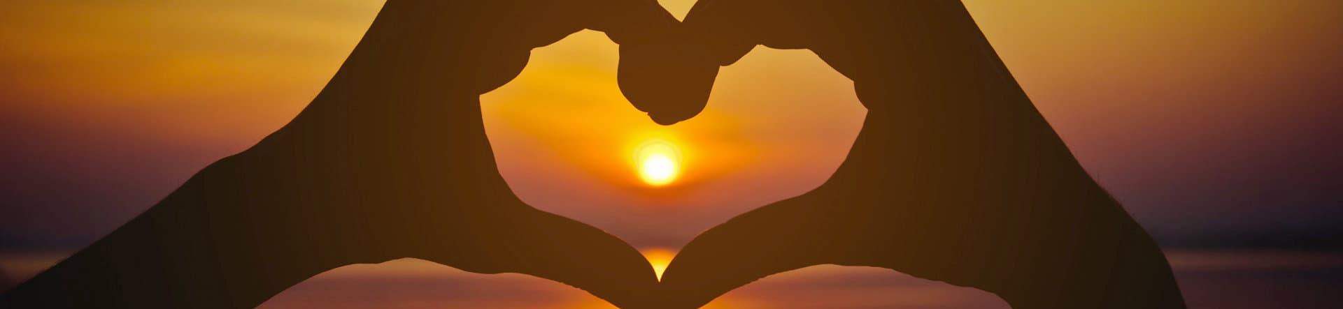 heart on hand over sunset